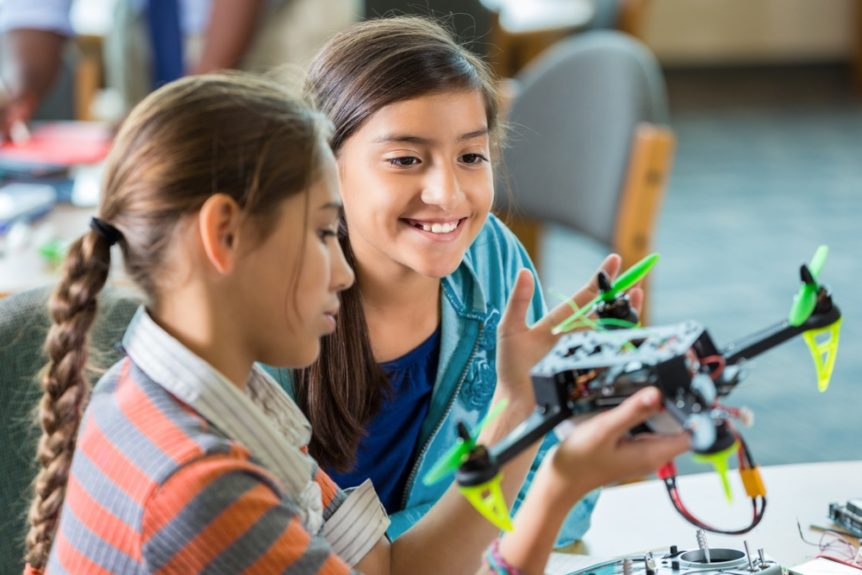Elementary age Hispanic little girls are using drones during after school science club or program. Students are studying science, technology, engineering, and math in public elementary school library makerspace.